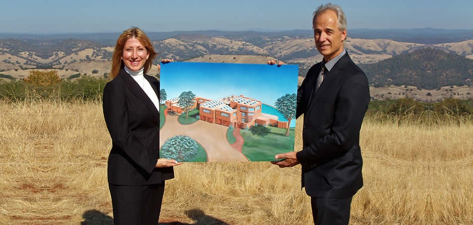 Oct 25, 2008<br/><br/>Briana Alhadeff and Nicholas Nikiforuk display one of the original renderings, set against the expansive northeast facing landscape.  The rendering is displayed in the exact location of where the home will be built and its orientation.